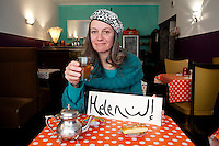 Hélène, a volunteer guide with the Marseille Provence Greeters, poses for the photographer at restaurant 'La Menthe Sauvage', Rue Guy Mocquet, Marseille, France, 04 February 2013. Her name is painted in Arabic alongside the English version on the card.