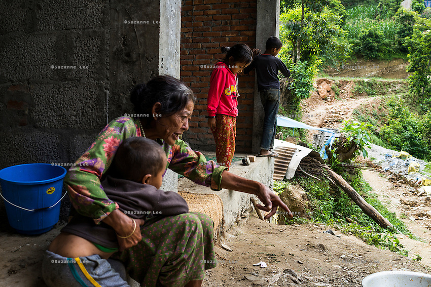 Monika (7, in red) hangs around as her grandmother Bhagawati Baniya (56) plays with her cousins in their temporary home in Chautara, Sindhupalchowk, Nepal on 29 June 2015. The three girls lost their mother during the April 25th earthquake that completely levelled their house. Aastha was buried under the rubble together with her mother but Aastha survived. As their father Ratna Baniya (28) cannot care for the children on his own, SOS Childrens Villages has since been supporting the grandmother with financial and social support so that she can manage to raise the children comfortably and ensure that they will all be schooled. Photo by Suzanne Lee for SOS Children's Villages
