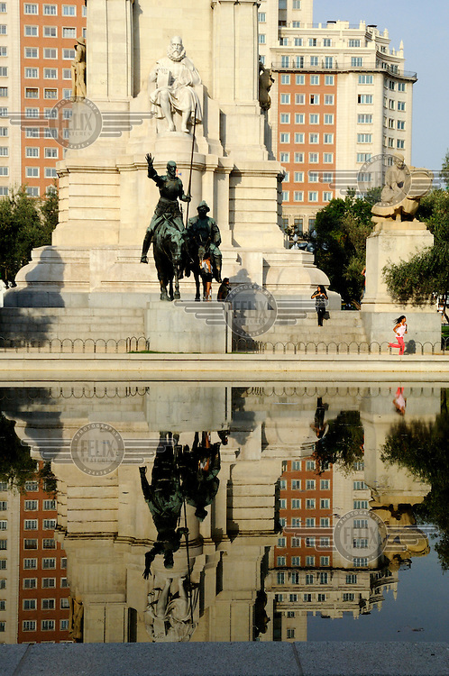 A statue of Don Quixote and Sancho Panza at the base of the monument to Cervantes is reflected in a puddle in the Plaza de Espana.