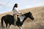 A Native American Indian man sitting bareback on a horse in traditional Sioux Indian clothing using a War Bridle in South Dakota