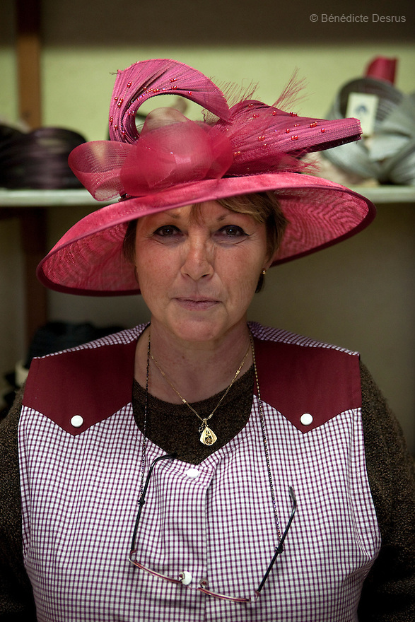 9 december 2009 - Coustilleres' hat factory, Septfonds, France - Michele Coustilleres, wife of the owner, is wearing a woman hat at the Coustilleres' hat Factory..Septfonds is the heart of French straw hat making, due to its very ancient hatter tradition. The hat making industry had its commercial peak in the late 19th century..Coustillères is a family owned hat making factory that has been making straw hats in Septfonds for nearly 100 years. They make hats from straw, felt, and cloth as well as caps. The current owner is Jean-Claude Coustilleres. He is one of the last hat makers of the region..The straw hat making process is very labor intensive and numerous hands are involved. Nearly all of the equipment is over 100 years old, they use the original presses and tools including aluminium molds and sewing machines and dye their own straw continuing the traditional methods of manufacturing. The hat blocking and shaping, straw braids construction and dyeing are all done by hand..The company works on behalf of fashion houses and makes a variety of regional and historical hats. It produces 2 collections a year distributed by a network of salespeople and through a catalog to clients around the world. Photo credit: Benedicte Desrus