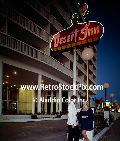 A young couple standing by the neon sign at dusk.Desert Inn, Daytona Beach Florida