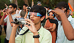 Crowds of people armed with special glasses to prevent eye damage watch as the moon passes the face of the sun during the longest solar eclipse this century. The eclipse drew big crowds to New Delhi's Nehru Planatarium to see the spectacular views. The eclipse was seen across India before focus shifted towards China and Japan. Many people stayed indoors for supersticious reasons whilst others celebrated with prayer and ceremony.