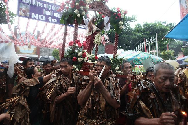 "A steady rain is pouring as men hoist a statue of St. John the Baptist and begin a parade through nearby streets during the annual Taong Putik, or ""mud people,"" festival in Bibiclat, on Luzon island,  Philippines. The festival honors St. John the Baptist, and devotees cover themselves in mud, banana leaves and vines to symbolize the animal skins he wore in the Bible. After the procession, the devotees strip off their ritual garments and wash themselves clean. June 24, 2011."