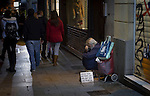 A homeless man begging on a street in central Madrid..