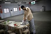 25 year old Chinese interpreter, Yuan Lei at the dining hall of the Chinese Colony in the Adani Power plant in Mundra port industrial city of Gujarat, India. Indian power companies have handed out dozens of major contracts to Chinese firms since 2008. Adani Power Ltd have built elaborate Chinatowns to accommodate Chinese workers, complete with Chinese chefs, ping pong tables and Chinese television. Chinese companies now supply equipment for about 25% of the 80,000 megawatts in new capacity.