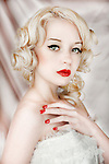 close up of delicate blonde girl in corset with red lipstick and nails looking at camera