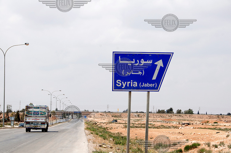 A road sign points the way to 'Syria' on a road near Zaatari, the site of a refugee camp for Syrian refugees who have fled to Jordan due to the the civil war. /Felix Features