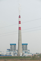 Daytime vertical view from a train of a smokestack at a commercial manufacturing facility near Píngyáo county of the Jìnzhōng District in Shānxī Province, China  © LAN