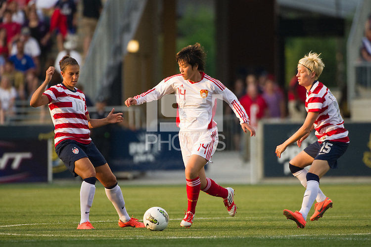 Liu Shukun (14) of China PR (CHN) is marked by Carli Lloyd (10) and Megan Rapinoe (15) of the United States (USA). The United States (USA) women defeated China PR (CHN) 4-1 during an international friendly at PPL Park in Chester, PA, on May 27, 2012.