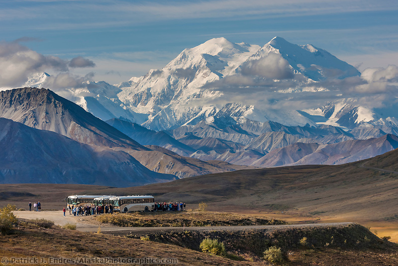 Tourists on buses stop at the Stony Dome lookout to view the massive Mt Denali, visible in the distance, Denali National Park, Interior, Alaska.
