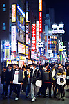Young people at night in the streets of Tokyo, Shibuya, Udagawacho with shining colorful street lights and shop signs. Tokyo city night life, Japan 2017.