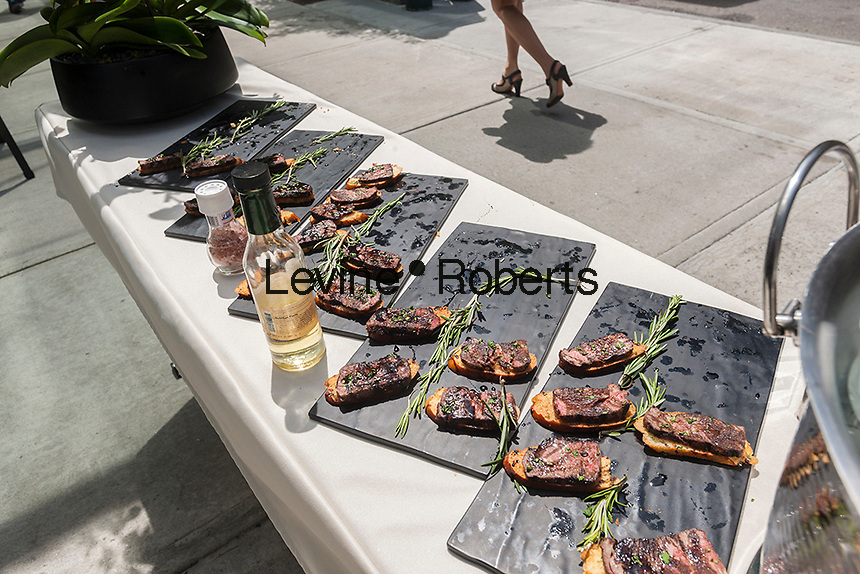 Fashion Bar Restaurant serves steak with truffle oil after the unveiling of the new wayfinding kiosks that stand at either end of Restaurant Row in New York, West 46th street between 8th and 9th Avenues, on Tuesday May 16, 2017. At least four years in the making the illuminated kiosks show the names of the many eateries that populate the street. The unveiling is just in time for the Taste of Times Square event taking place on the street on June 5. (© Richard B. Levine)