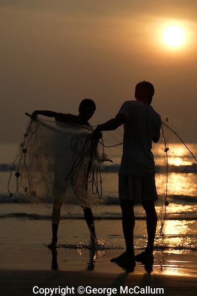 Pair of Beach fishermen folding  Gill net on pole, Goa, Arabian sea, India