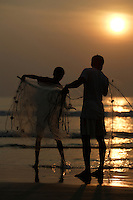 Pair of Beach fishermen folding  Gill net on pole, Goa, Arabian sea, India