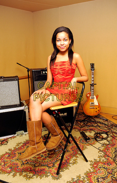 DIONNE BROMFIELD.Amy Winehouse's goddaughter, aged 13, pictured at her North London recording studio, London, England..March 6th, 2009.full length red dress brown ugg boots sitting blomfield.CAP/FIN.©Steve Finn/Capital Pictures