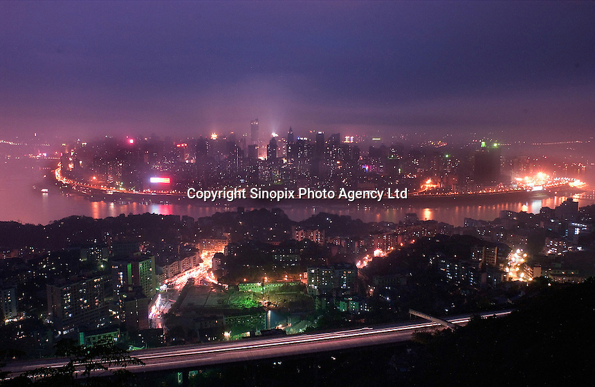 """Chongqing city overlooking the Yangtze river at night. Chongqing is China's largest city and is often termed a """"super-city"""". It is at the far shore of the 600 km long Three Gorges Dam and is the """"gateway to western China"""". Large sums of money are being pumped into the area and infrastructural projects and building development is ongoing.."""