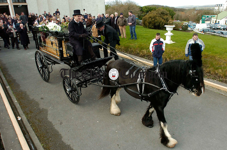 The remains of local man Michael Neylon are brought from Ennistymon church by horse drawn hearse to his final resting place. Photograph by John Kelly.
