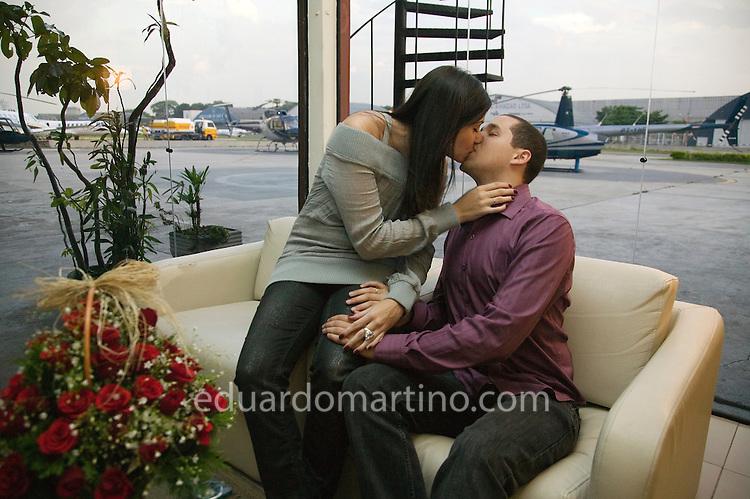 A young couple enjoy each other's company at a VIP room, with a bottle of champagne. They are about to depart on a night tour flying over Sao Paulo for 17 minutes, landing on Sofitel's helipad. They will then have a special dinner and a romantic night at the hotel. This service, called Night Air is one of the many types of helicopter use becoming increasingly popular in Sao Paulo. .photo: Eduardo Martino / 01.02.2008