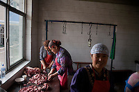 Hui minority women prepare meat for a wedding banquet in a mosque in Pingliang, Gansu, China.  The mosque is predominantly attended by members of the Hui ethnic minority.