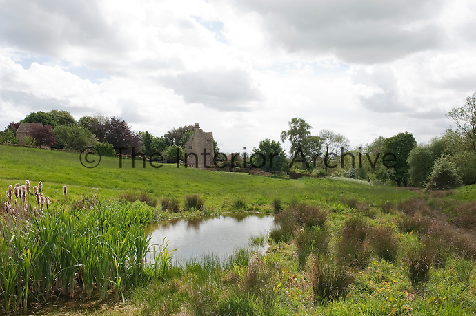 A side view of the idyllic setting of the house from the ponds in the meadow