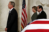 From left to right, United States President George W. Bush, First Lady Laura Bush and Supreme Court Judge Antonin Scalia walks away from Chief Justice William Rehnquist's casket Sept. 6, 2005 in the Great Hall of the Supreme Court in Washington, DC. Rehnquist's casket will lie in repose at the court until the next morning and he will be buried in a private ceremony at Arlington Cemetery that afternoon.<br /> Credit: Chip Somodevilla / Pool via CNP