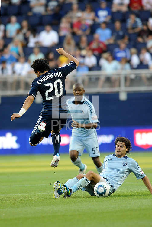 Davide Chiumiento (20)  Vancouver Whitecaps jumps over the challenge from Graham Zusi Sporting KC... Sporting KC defeated Vancouver Whitecaps 2-1 at LIVESTRONG Sporting Park, Kansas City, Kanas.