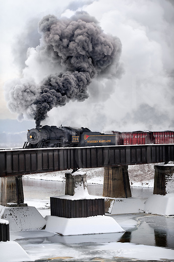 It was a crisp and overcast January morning as this antique steam train left her yard and shops to cross over the partly frozen Potomac River and chuff into the station at Cumberland, Maryland. Black and white smoke and steam curling high overhead tells the air temperature and her speed as she pulls a string of vintage freight cars the first half mile of the trip. Today&rsquo;s working day for this old timer would last until dark with many run-bys during a photographer&rsquo;s special going up the mountain in the cold with no sunlight.<br /> <br /> The day was gray with pervasive damp that works it way into your bones along with the penetrating cold, but it was that same winter air that made for impressive smoke and steam clouds. The chill and cold feet were worth going through to get shots showing the way heavy freight was pushed over these mountains over a hundred years ago by the will of man and machine. Not only is seeing this locomotive in action fun, but the full experience of smelling burning coal and having the cinders hit your skin while the sharp whistle screams warnings at the crossings is a deep one. It&rsquo;s easy to be transported by this time machine, and imagination is truly it&rsquo;s modern day freight.<br /> <br /> The Western Maryland is long gone as a fallen flag railroad, but lives on in this tourist version as the Western Maryland Scenic Railroad with heritage steam as the focus. You can take a beautiful mountain ride on this train and get tickets by visiting https://www.wmsr.com/