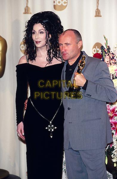 CHER & PHIL COLLINS.Ref:9468.oscars, awards, award winner, black dress, half length, half-length.www.capitalpictures.com.sales@capitalpictures.com.© Capital Pictures