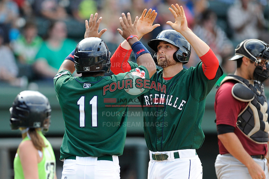 First baseman Sam Travis (28) of the Greenville Drive, right, is greeted at home by Wendell Rijo (11) after hitting a home run in a game against the Savannah Sand Gnats on Sunday, August 24, 2014, at Fluor Field at the West End in Greenville, South Carolina. Travis is a second-round pick of the Boston Red Sox in the 2014 First-Year Player Draft out of Indiana University. Greenville won, 8-5. (Tom Priddy/Four Seam Images)