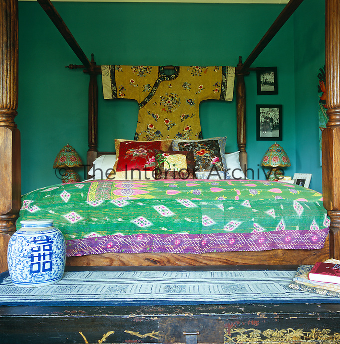 This bedroom has a kimono as a headboard draped over a mahogany four-poster bed which is covered in bright textiles