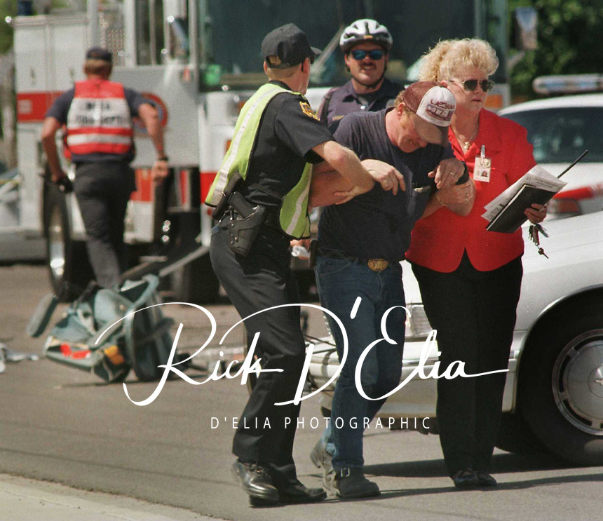 A mesa Police officer and unidentified woman help a distraught Edwin Duncan away from the scene where his truck colided with a woman ina wheel chair at Center and Broadway.