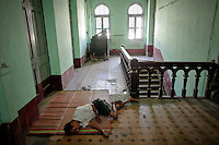 A man sleeps in hallway of a deteriorating colonial era building in central Yangon April 12, 2012. Myanmar, also known as Burma, was a British colony until winning its independence in 1948 thanks to the late national hero General Aung San, the father of democracy icon Aung San Suu Kyi. Yangon, also known as Rangoon, was the capital of British Burma and a major port between Calcutta and Singapore. It owes its current appearance to British planners, with streets laid out in a grid, interspersed with churches, temples and grand but neglected municipal buildings. British Prime Minister David Cameron will push for more reforms during a landmark visit to Myanmar later on Friday, the first by a major Western leader in 50 years as countries jockey for business and influence in the long isolated state.  REUTERS/Damir Sagolj (MYANMAR)