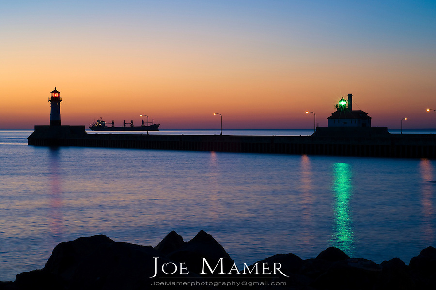A ship awaits entry to Duluth Harbor with the canal lighthouses silhouetted against the glow of the sunrise.