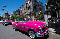 Havana Cuba pink classic 1950s auto in beautiful neighborhood of Habana parked