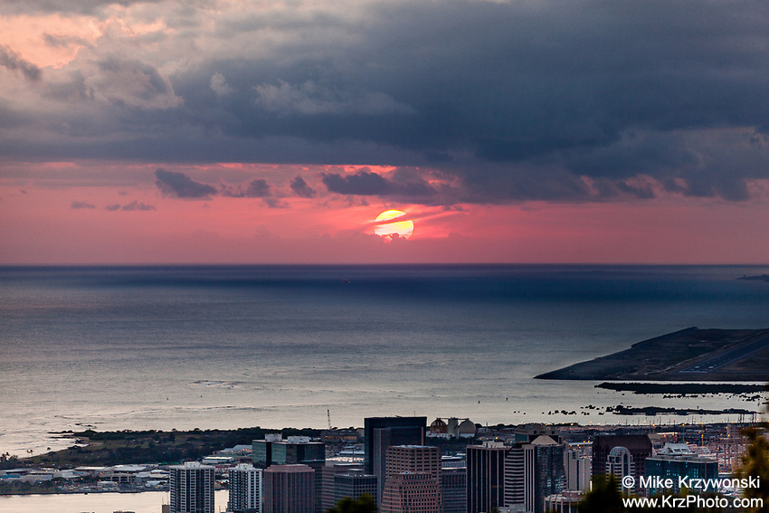 Aerial view of a red sun setting over the ocean behind buildings in downtown Honolulu as seen from Tantalus Lookout, Puu Ualakaa State Park