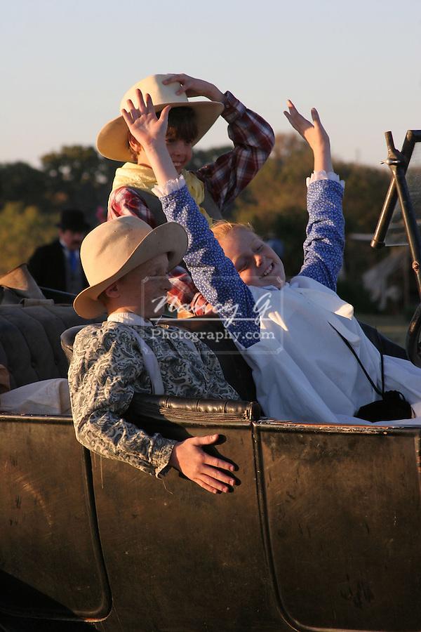 Children enjoying a joy ride in an old car.  No hands