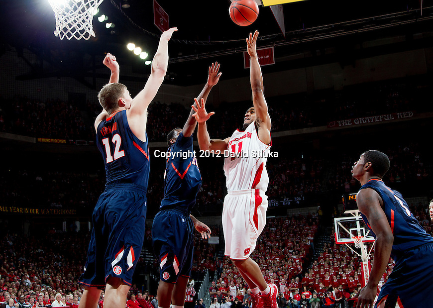 Wisconsin Badgers guard Jordan Taylor (11) shoots the ball over two defenders during a Big Ten Conference NCAA college basketball game against the Illinois Fighting Illini on Sunday, March 4, 2012 in Madison, Wisconsin. The Badgers won 70-56. (Photo by David Stluka)