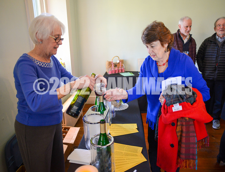 From left, Nancy Macur of Peave Valley Winery pours a glass of wine for Barbara Keiffer of Buckingham, Pa. at the Bucks County Designer House Empty House Party Sunday, February 26, 2017 in Buckingham, Pennsylvania. (Photo by William Thomas Cain)