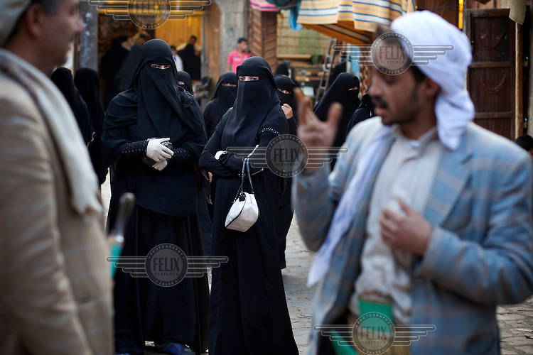Women look on as men have a conversation on a street in the old city souk.