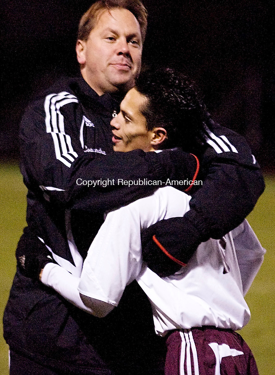 NAUGATUCK, CT--07 November 07--110707TJ05 - FOR ACTION MAN Naugatuck's John Fernandez (7), who scored Naugatuck's only goal, gets a hug from assistant coach Jose Sendra after Naugatuck High School's 1-0 victory over Masuk High School in the first round of the CIAC class LL boys tournament in Naugatuck, Conn., on Wednesday, November 7, 2007. T.J. Kirkpatrick/Republican-American