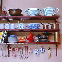 Metal shelves along one wall of the kitchen provide useful storage for oversize ceramic bowls, containers and random kitchen items