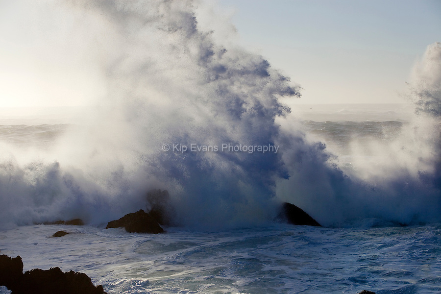 A large wave crashes over rocks along the California Coast.