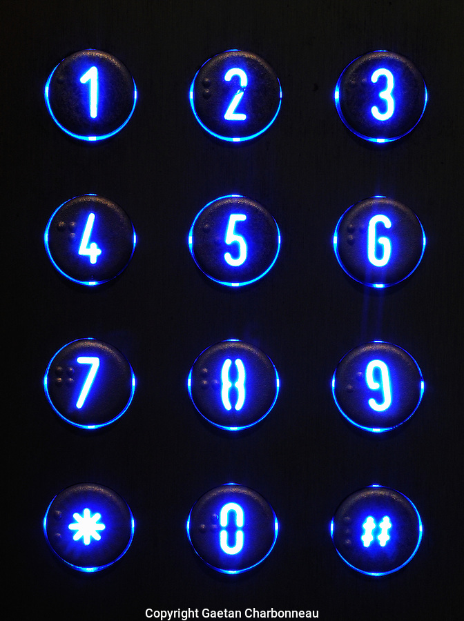 Extreme close up of a building intercom illuminated at night