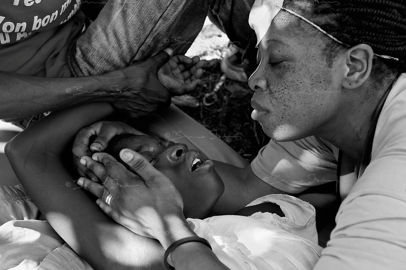 Port au Prince, Haiti, Jan 16 2010.Marie Marthe Doval, 11 suffers from multiple open fractures of her right leg; she is in great pain as a Canadian volunteer aid worker changes her dressing and cleans her terrible wound without any pain killer. The Central University Hospital is overwhelmed by the number of victims, many stay in the garden with almost no treatment for their often serious injuries as the hospital has run out of most medecine such as analgesics.