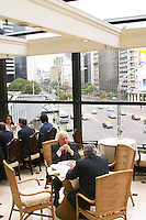 In the Sheraton Hotel Restaurant lunch guest looking out through big windows on to the traffic on the wide avenue outside. Buenos Aires Argentina, South America