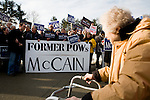 A woman passes by supporters of Republican presidential hopeful Sen. John McCain (R-Ariz.) at a polling station in Nashua, N.H., on Tuesday, Jan. 8, 2008.