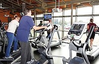 Nancy Beecher works out in the exercise room at Warner Park Community & Recreation Center. The exercise area features modern equipment such as elliptical trainers and treadmills.