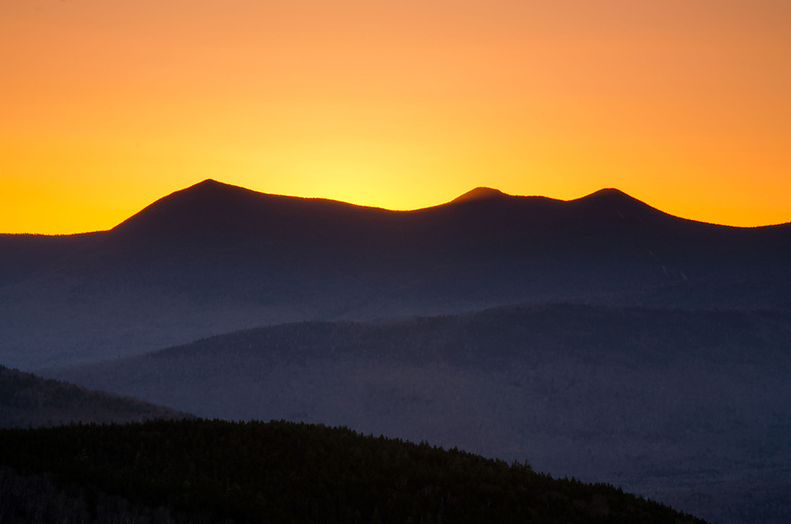 The sky turns to gold moments before sunrise over Mt Tripyramid in New Hampshire's White Mountains.