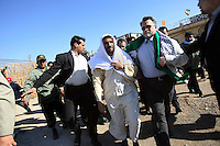 Wearing traditional Arab dress, Iranian President Mahmoud Ahmadinejad walks to a public meeting in the city of Susangerd in the coastal province of Khuzestan. As a way of attracting the numerous important minority groups in Iran to the Islamic Republic's Persian-dominated system, Ahmadinejad occasionally dons local costume in the places where he visits.